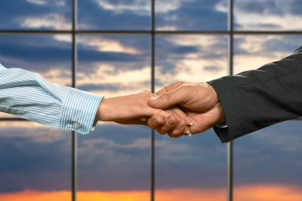 businessman-shakes-young-lady-s-hand-woman-s-handshake-sunrise-background-protection-trust-our-new-ally